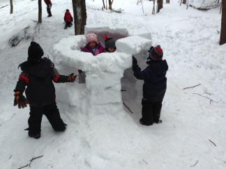 Ottauquechee students building a forest igloo.